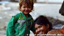 An indian child with her mother who begs for livinghood reacts and smiles in camera,in Allahabad on July 5,2015.According to UNICEF report,Children living in poverty experience deprivation of the material, spiritual and emotional resources needed to survive, develop and thrive, leaving them unable to enjoy their rights, achieve their full potential or participate as full and equal members of society. (Photo by Ritesh Shukla/NurPhoto)