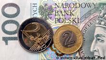 Slubice (Polen): Auf einem polnischen 100-Zloty-Schein liegen am 17.12.2001 im polnischen Slubice, der Nachbarstadt von Frankfurt (Oder) in Brandenburg, eine Zwei-Euro-Münze (l) und eine Zwei-Zloty-Münze. Wenn in Deutschland der Euro als Zahlungsmittel zum Einsatz kommt, nehmen einige Händler kurz hinter der deutsch-polnischen Grenze eine Zeit lang nicht nur diesen und Zloty entgegen, sondern auch noch die Deutsche Mark. Im Landesinnern von Polen sollte die deutsche Kundschaft jedoch für alle Fälle die Landeswährung oder eine Kreditkarte bereit haben. Das Personal in Polens Banken und Wechselstuben bereitet sich intensiv auf die Euro-Münzen und -Scheine vor. Ab Januar 2002 soll die Deutsche Mark in den polnischen Banken nicht mehr angenommen werden. (FFO01-191201)