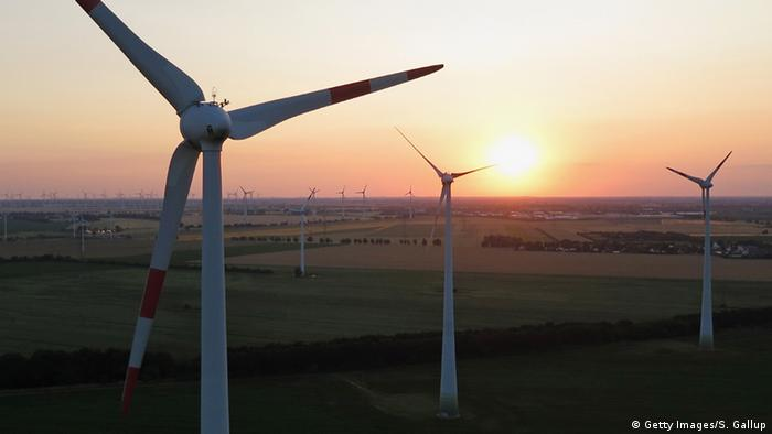 In this aerial view electricity-producing wind turbines spin at a wind farm