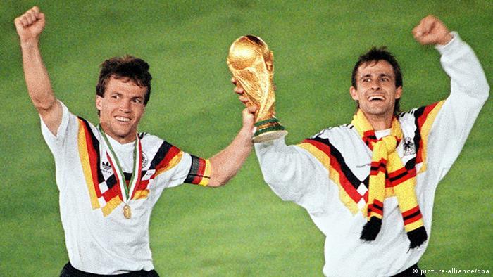 Die Fußballspieler Lothar Matthäus und Pierre Littbarksi mit dem Pokal der Weltmeisterschaft 1990