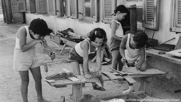 Children use tools to work on wood crafts outside a house (G. Pickow/Three Lions/Hulton Archive/Getty Images)