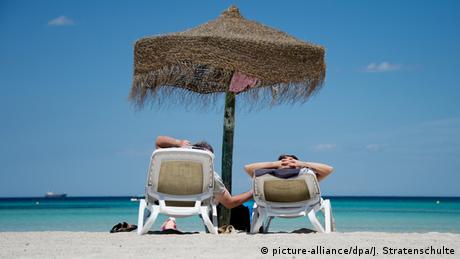 Zwei Personen liegen am Strand unter einem Sonnenschirm auf Liegen