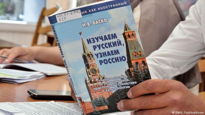 Учебник русского языка для иностранцев в руках у мужчины