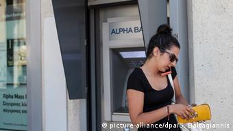 Жительница Афин у банкомата Alpha Bank
