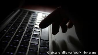 Рука на клавиатуре компьютера в темноте - фото, символизирующее киберпреступность