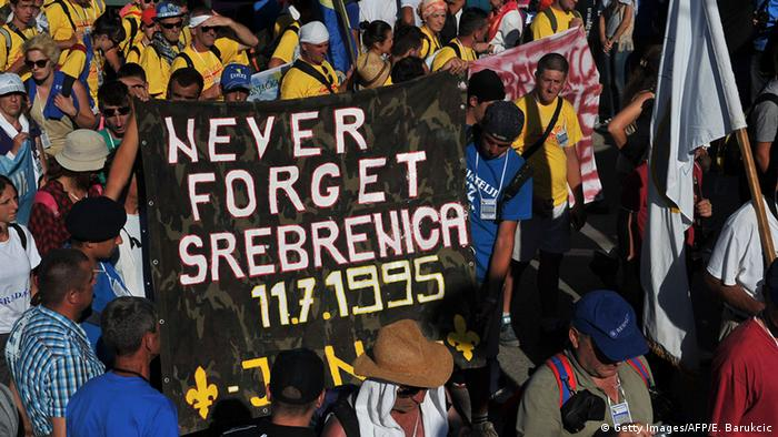 Bosnian protesters hold a banner reading 'never forget Srebrenica' during the Srebrenica Peace March near the city center of Srebrenica on July 10, 2015 (Photo: ELVIS BARUKCIC/AFP/Getty Images)