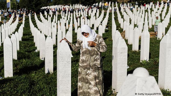 A Bosnian woman mourns at the grave of a relative at Potocari Memorial Center near Srebrenica