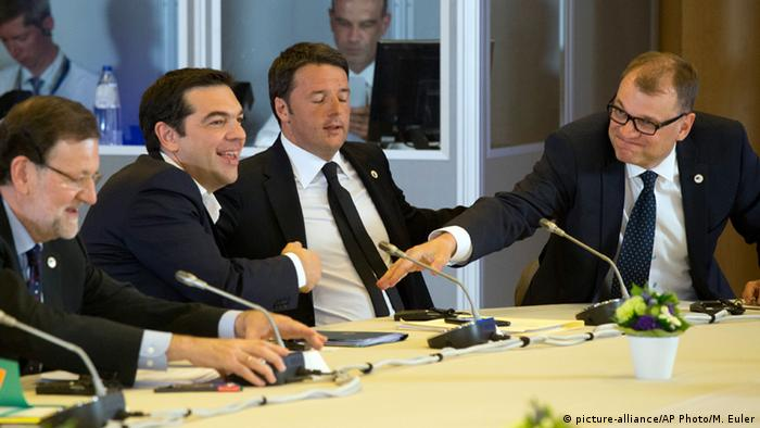 Juha Sipilä and Alexis Tsipras attempting to shake hands across a table. (Photo: AP Photo/Michel Euler)