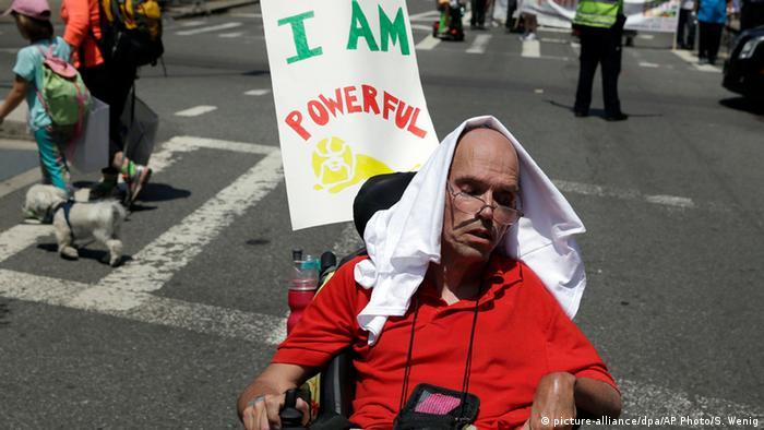GerardMills sitzt im Rollstuhl und nimmt mit dem Schild Ich bin stark an der Parade teil. (Foto: AP)