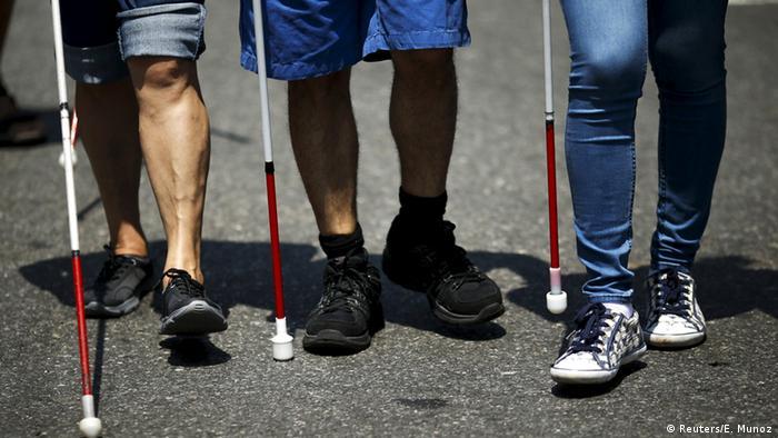 Drei Sehbehinderte mit ihren Blindenstöcken bei der Parade. (Foto: Reuters)