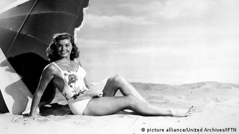 Esther Williams posing in a suit on sand