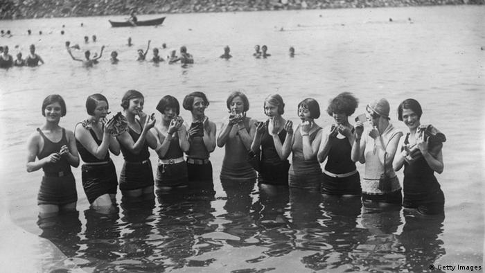 Women with page-boy haircuts and shorter bathing suits standing in the water