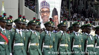 Nigerian military in front of poster of Nigerian President Buhari