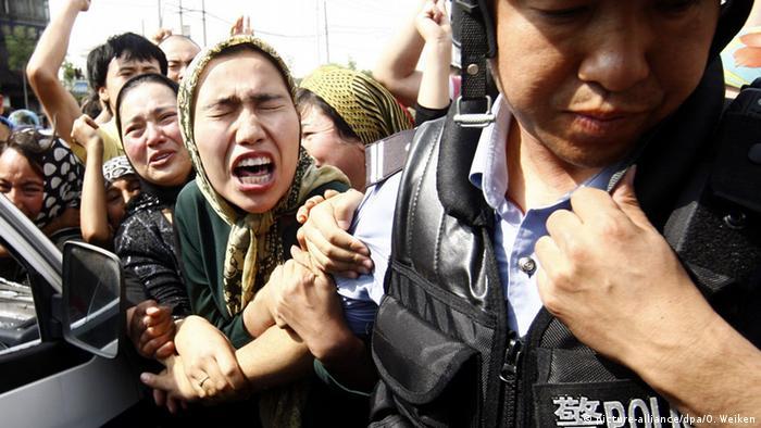 نساء من الأقلية الإيغورية المسلمة في الصين في مواجهة مع شرطي صيني (صورة من الأرشيف)