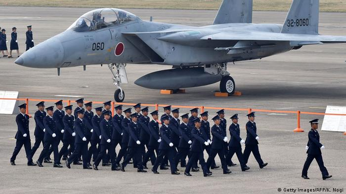 Air servicemen of the Japan Self-Defense Force walk past a F-15J/DJ fighter aircraft on a runway prior to a review ceremony at the Japan Air Self-Defense Force's Hyakuri air base in Omitama, Ibaraki prefecture on October 26, 2014 (Photo: KAZUHIRO NOGI/AFP/Getty Images)