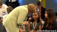 Angela Merkel tröstet palästinensisches Mädchen. Mi, 15.7.2015: Gut leben in Deutschland: Im Rahmen des Bürgerdialogs hat Kanzlerin Merkel mit Schülerinnen und Schülern diskutiert. Screenshot von Videomaterial. Quelle: bundesregierung.de