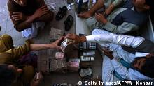 Afghan money changers count Afghani bank notes at the currency exchange Sarayee Shahzada market in Kabul on June 29, 2015. Afghani exchange rate against USD is one USD equal to 6.75 Afghani. The exchange rate against other currencies are based by the Central Bank of Afghanistan. AFP PHOTO / Wakil Kohsar (Photo credit should read WAKIL KOHSAR/AFP/Getty Images)