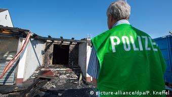 A police officer looks at a burned house