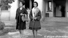 Zwei westlich gekleidete junge Frauen verlassen im Oktober 1962 das Studiogebäude von Radio Kabul in der afghanischen Hauptstadt. Nach der Übernahme der Macht durch die fundamentalistischen Taliban Mitte der 90-er Jahre ist es für afghanische Frauen unmöglich geworden, sich in westlicher Kleidung zu zeigen oder gar am öffentlichen Leben teilzunehmen. Das Tragen der traditionellen Burqa (Körperschleier) ist Pflicht. Mädchen erhalten so gut wie keine Schulbildung, Frauenarbeit ist verboten und die medizinische Versorgung mangelhaft.