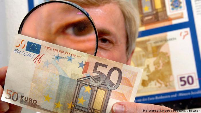 Scrutinizing a 50-euro bill (picture-alliance/dpa/dpaweb/J. Büttner)