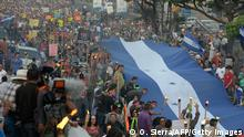 17.07.2015 Demonstrators known as 'indignados' -- the indignant ones -- and supporters of the leftist Libre party march in demand of the resignation of Honduran President Juan Orlando Hernandez over an ongoing corruption scandal, towards the US embassy where a group is holding a hunger strike, in Tegucigalpa on July 17, 2015. The demonstrators, who have been marching and protesting since May, demand the creation of a United Nations International Commission Against Impunity and reject any dialogue with the president. The protesters accuse Hernandez of receiving about $90 million of more than $300 million they say was skimmed from poverty-wracked Honduras' public health system for his campaign. AFP PHOTO / ORLANDO SIERRA (Photo credit should read ORLANDO SIERRA/AFP/Getty Images)