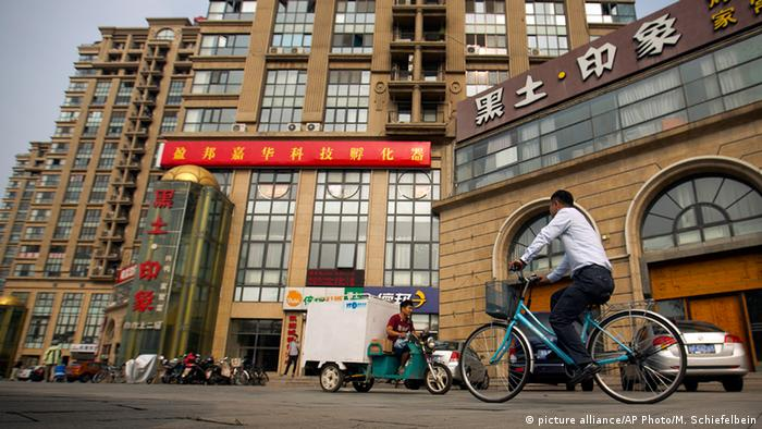 A delivery cart and cyclist ride past a building housing the Fengrui law firm in Beijing. Since late May, police across China have detained and called in at least 215 rights lawyers and social activists, including many of Fengrui's lawyers (AP Photo/Mark Schiefelbein, File)