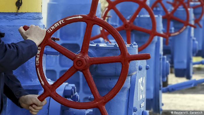 Рабочий крутит газовый кран на трубе
