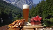 Weizenbier und Brotzeit vor Bergkulisse