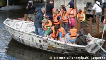 Schüler und Schülerinnen steigen am 20.07.2015 in einem Hafenbecken in Bremerhaven (Bremen) in ein von Bremerhavener Viertklässlern und Schiffsexperten selbst gebautes 5,40 Meter langes Papierboot. Foto: Carmen Jaspersen/dpa +++(c) dpa - Bildfunk+++