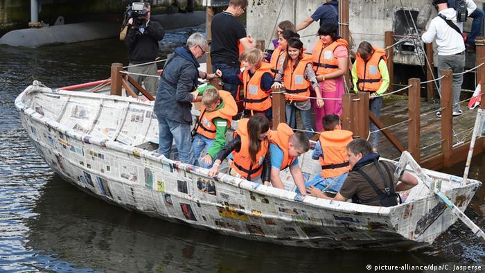 Schüler steigen in das selbstgebaute Papierboot. (Foto: dpa)