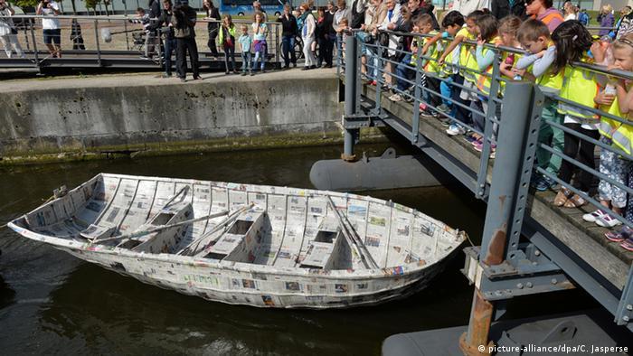 Kinder beobachten am Hafenbecken in Bremerhaven wie ein das Papierboot über das Wasser gezogen wird. Foto: (dpa)