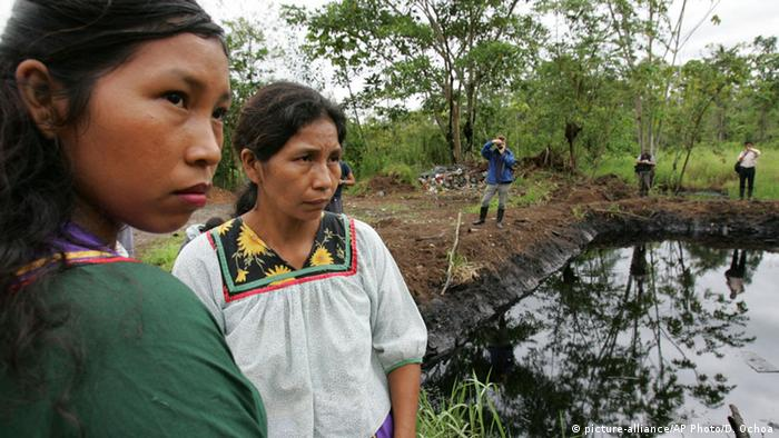 Cofan women stand near the remains of acontaminated open pit with oil at the Ecuadorean Amazonian region (Photo: AP/Dolores Ochoa R.)