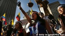 Protesters raise their hands in a demonstration against oil company Chevron demanding compensation (Getty Images/AFP/S. Platt)