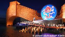 Sänger und Statisten treten vor der Kulisse der rot angestrahlten chinesischen Mauer bei der Fotoprobe der Oper Turandot am 17.07.2015 auf der Seebühne in Bregenz in Vorarlberg (Österreich) auf. Die Premiere der Oper von Puccini ist am 22.07.2015. Foto: Felix Kästle/dpa (zu dpa-Vorbericht «Bregenzer Festspiele werden mit Turandot eröffnet vom 22.07.2015) +++(c) dpa - Bildfunk+++
