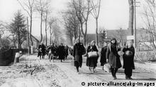 Trekking refugees pass through formerly German villages in northern Poland in 1946