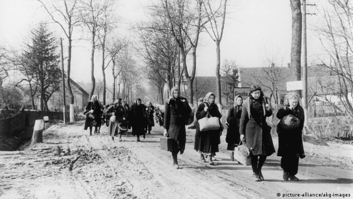Black and white photo of women carrying bundles walking through a Silesian village