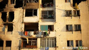 Palestinians look out a residential building that witnesses said was badly damaged by Israeli shelling in summer 2014 in Beit Lahiya in the northern Gaza Strip