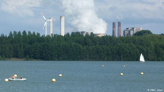 Schlauchboot und Segelbott auf dem Blausteinsee. Im HIntergrund das Braunkohlekraftwerk Weisweiler (Foto: Karin Jäger).