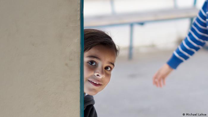 Schülerin schaut hinter einer Mauer hervor; Foto: DW Akademie
