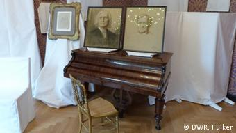 Portraits of Wagner and Liszt atop a piano along with other exhibits. Photo: Rick Fulker