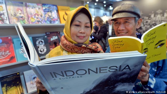 Zwei Indonesier mit Büchern über Indonesien (Foto: Hendrik Schmidt/dpa)