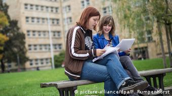 Две студентки сидят на скамейке