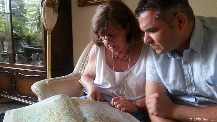 German woman with Syrian refugee looking at map