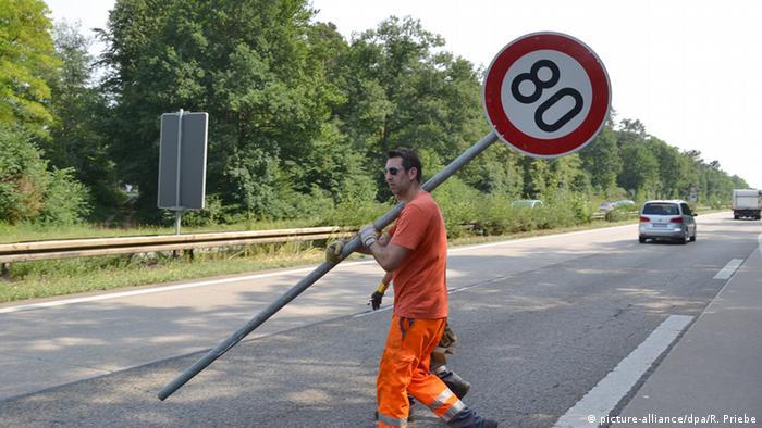 Ein Mitarbeiter der Autobahnmeisterei stellt an der Autobahn A5 bei Heidelberg ein Schild Tempolimit 80 Stundenkilometer auf