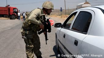 Soldier questioning someone in a white car ILYAS AKENGIN/AFP/Getty Images