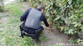 A policeman searches for drugs under a bush in Görlitzer Park