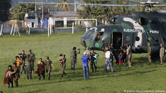 Zibilisten und Soldaten vor einem Militärhubschrauber
