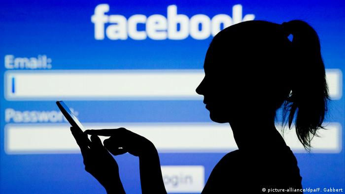 A silhouette of a woman with a floppy ponytail using a smartphone with her forefinger in front of a log-in screen displaying Facebook's blue-and-white logo