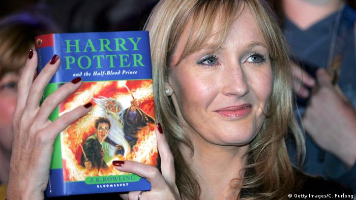 J.K. Rowling holds up a Harry Potter book (Getty Images/C. Furlong)