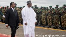 President of Cameroon Paul Biya (L) walks with his Nigerian counterpart Muhammadu Buhari following his arrival at the airport in Yaounde on July 29, 2015. Nigerian President Muhammadu Buhari arrived in neighbouring Cameroon for talks on how to combat the escalating regional threat from Boko Haram Islamists. Security was tight for the 24-hour visit, after a surge of Boko Haram violence in Cameroon including an unprecedented series of five suicide bombings in the far north. AFP PHOTO / REINNIER KAZE (Photo credit should read Reinnier KAZE/AFP/Getty Images)
